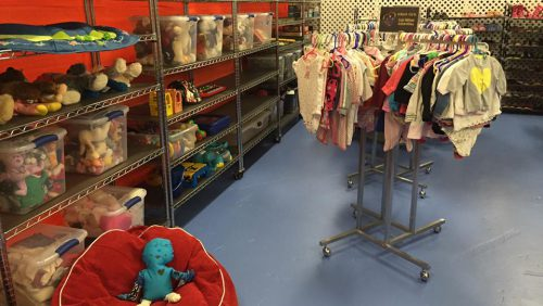 Clothing room with clothes on shelves and on a rack