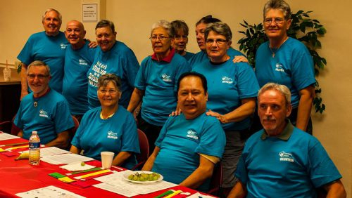 Group photo of volunteers at an event in front of a long table.