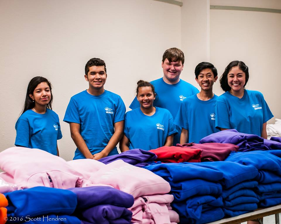Group of volunteers by stacked clothes