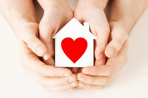 Hands holding a house with a heart in it