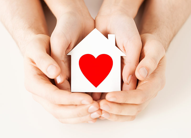 Hand holding home with heart inside
