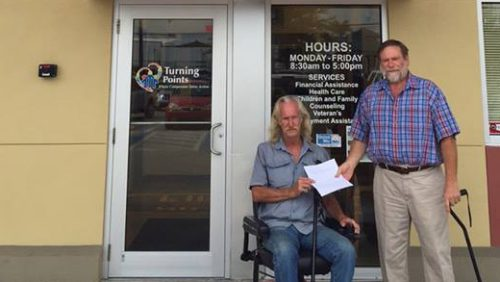 Man in a wheel chair receiving a document from a Turning Points employee