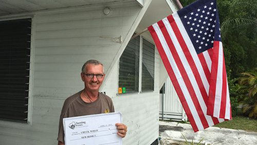 Man outside home holding a check from Turning Points