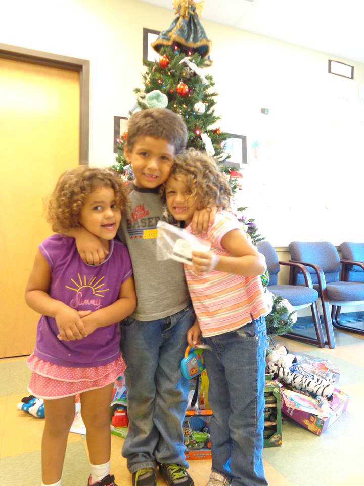 Kids by a Christmas tree with gifts under it at Turning Points
