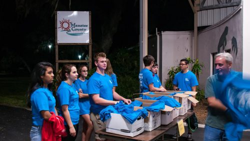 Group of volunteers by a table with turning points shirts.