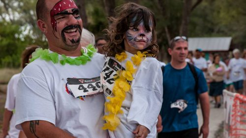 Man and daughter with painted faces.