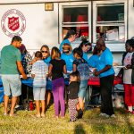 Volunteers in front of Salvation Army truck giving out food.